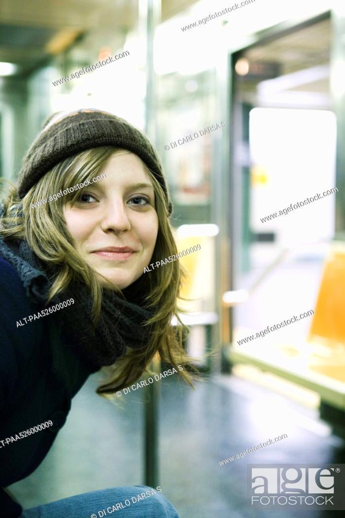 Stock Photo: Young woman riding subway, smiling at camera.