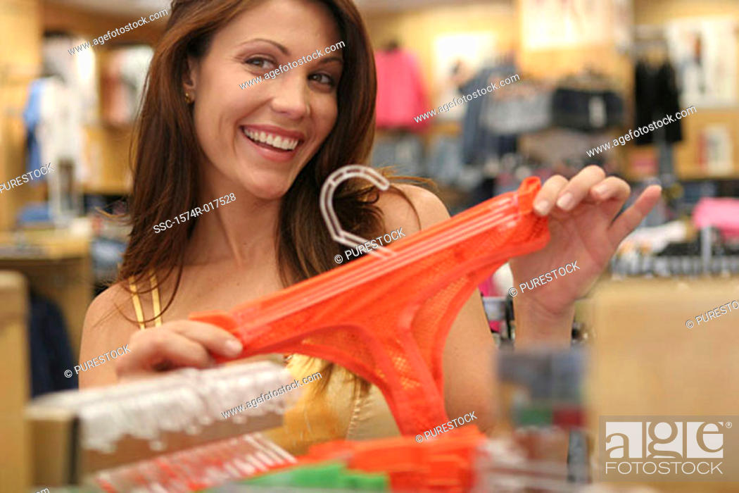 Stock Photo: Young woman holding underwear in a clothing store.