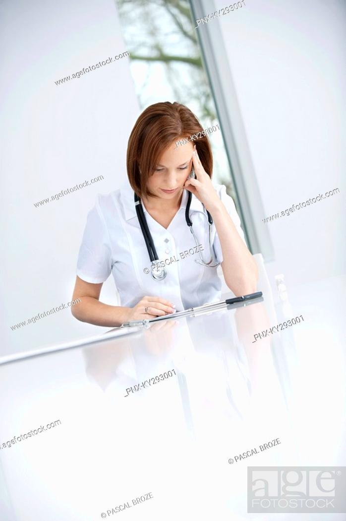 Stock Photo: Female doctor sitting in an office looking upset.