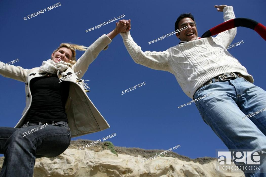 Stock Photo: Happy couple jumping in air.
