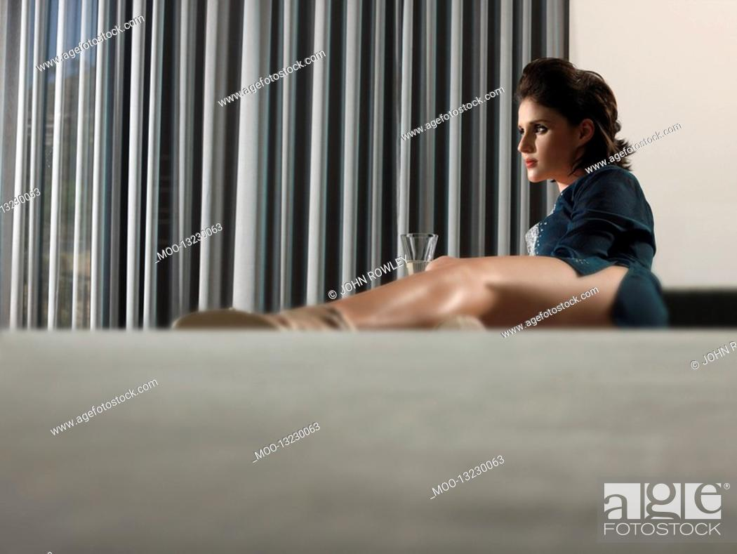 Stock Photo: Woman reclining with champagne in living room.