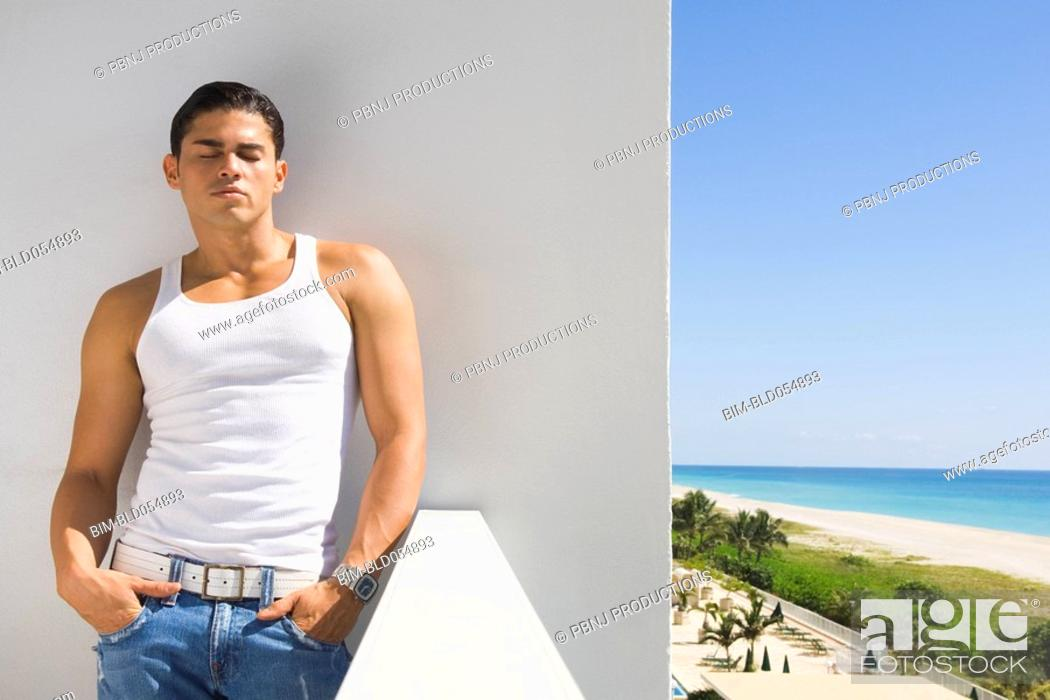 Stock Photo: Hispanic man leaning on balcony wall.