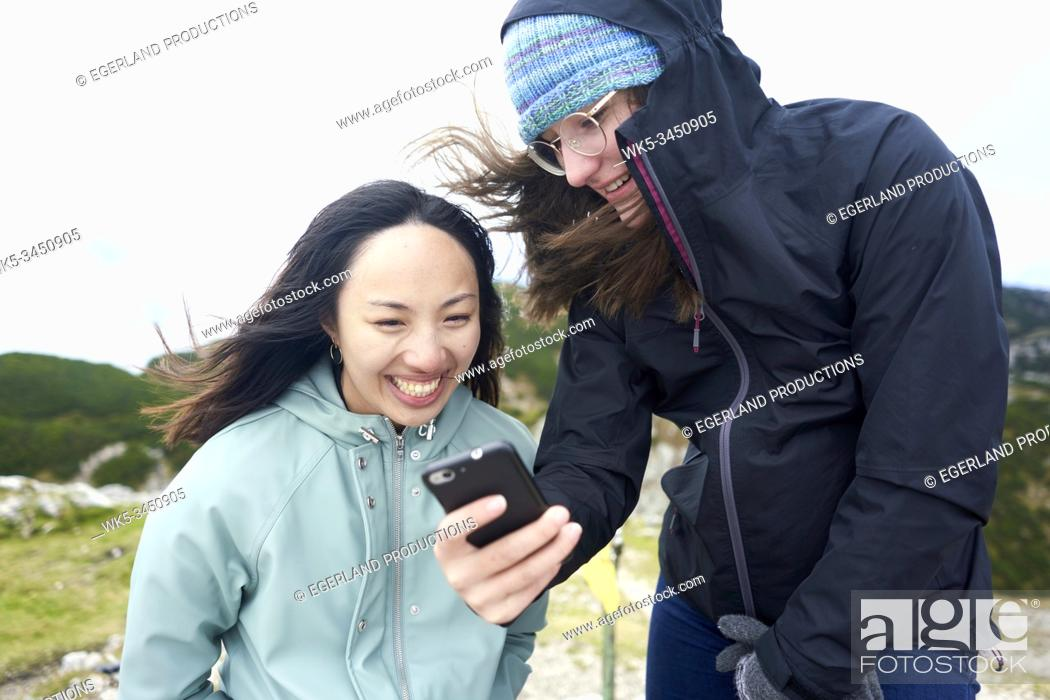 Imagen: friends looking at smartphone during hiking trip.