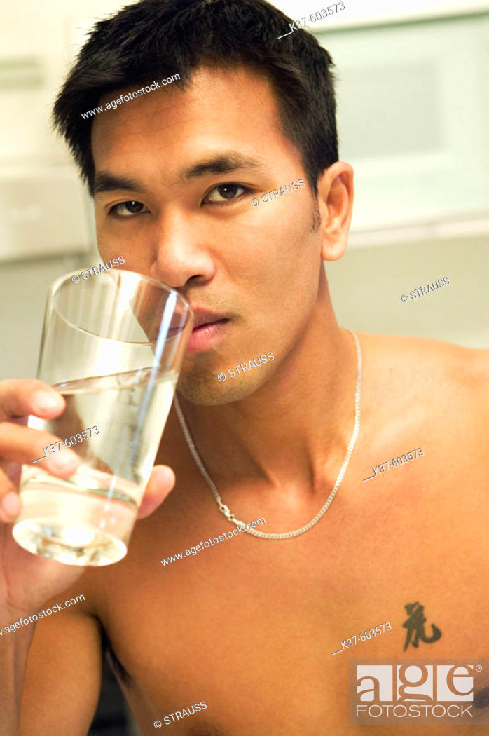 Stock Photo: 25-30 y/o Asian man in kitchen drinking water.