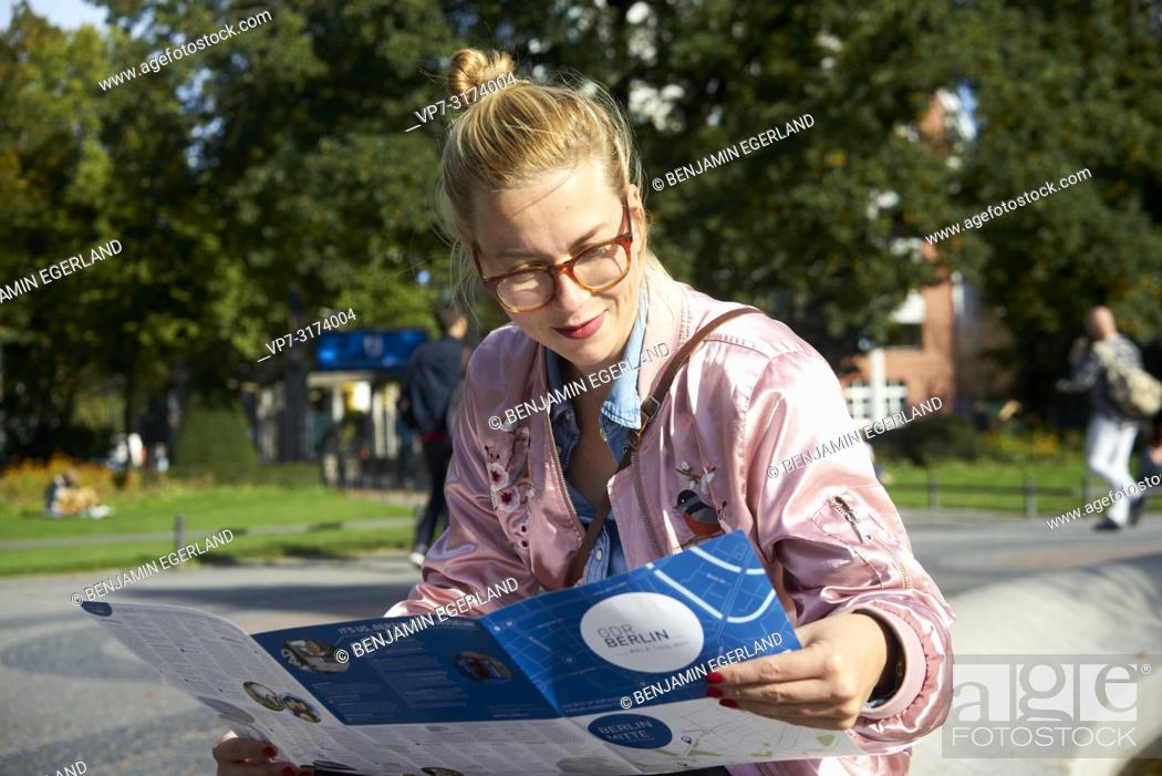 Stock Photo: Woman reading city guide map, in Berlin, Germany.