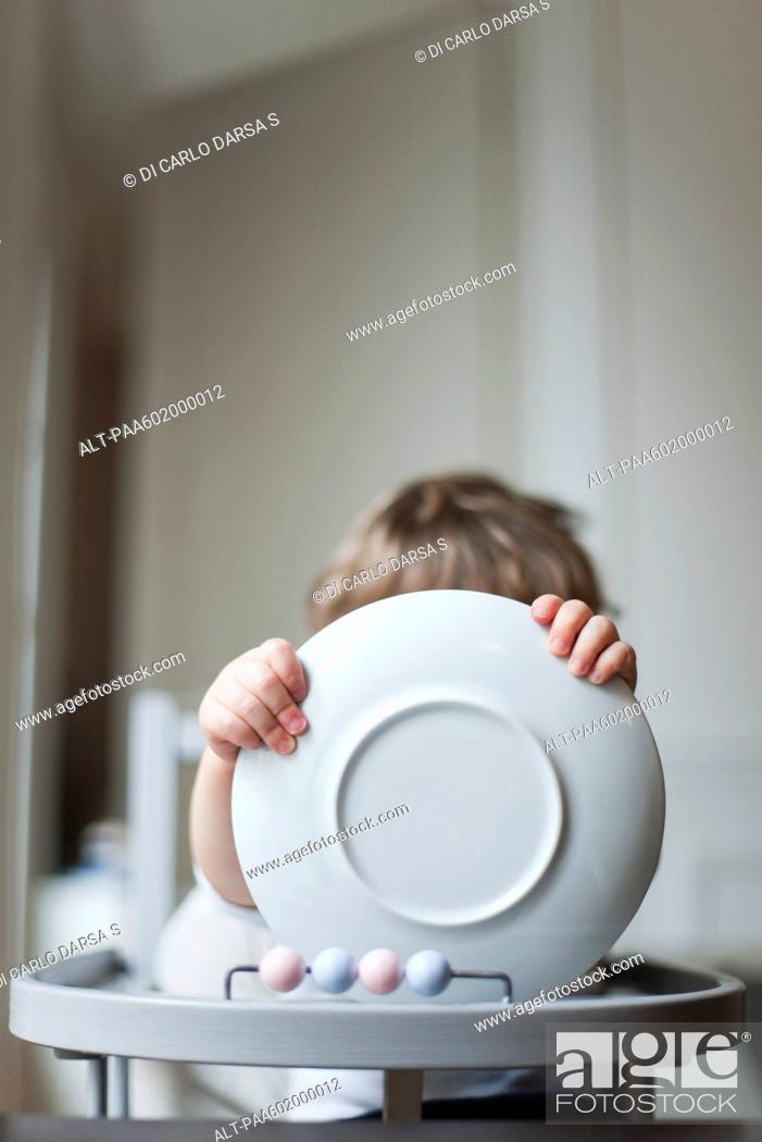 Stock Photo: Toddler sitting in high chair, holding plate in front of face.