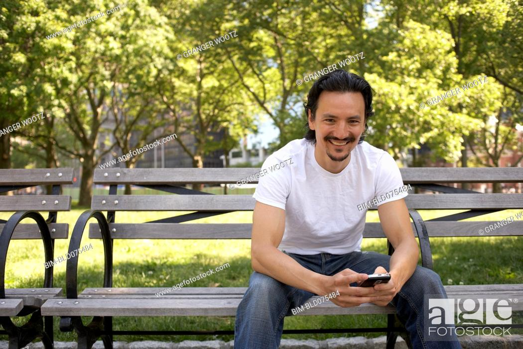 Stock Photo: Mixed race man holding cell phone on park bench.