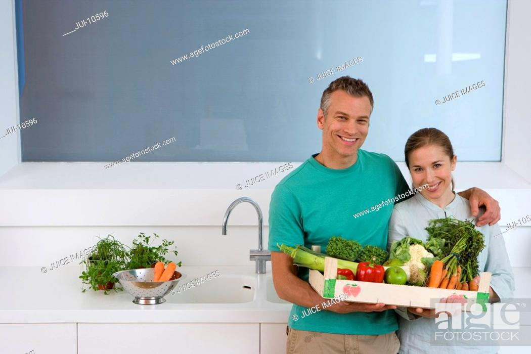 Stock Photo: Couple in kitchen holding box of vegetables, smiling, portrait, elevated view.