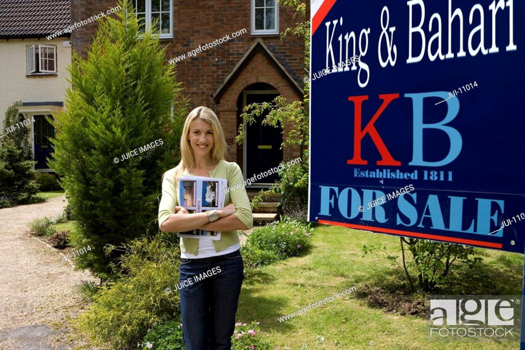 Stock Photo: Young woman with magazine outside house with 'for sale' sign, smiling, portrait.