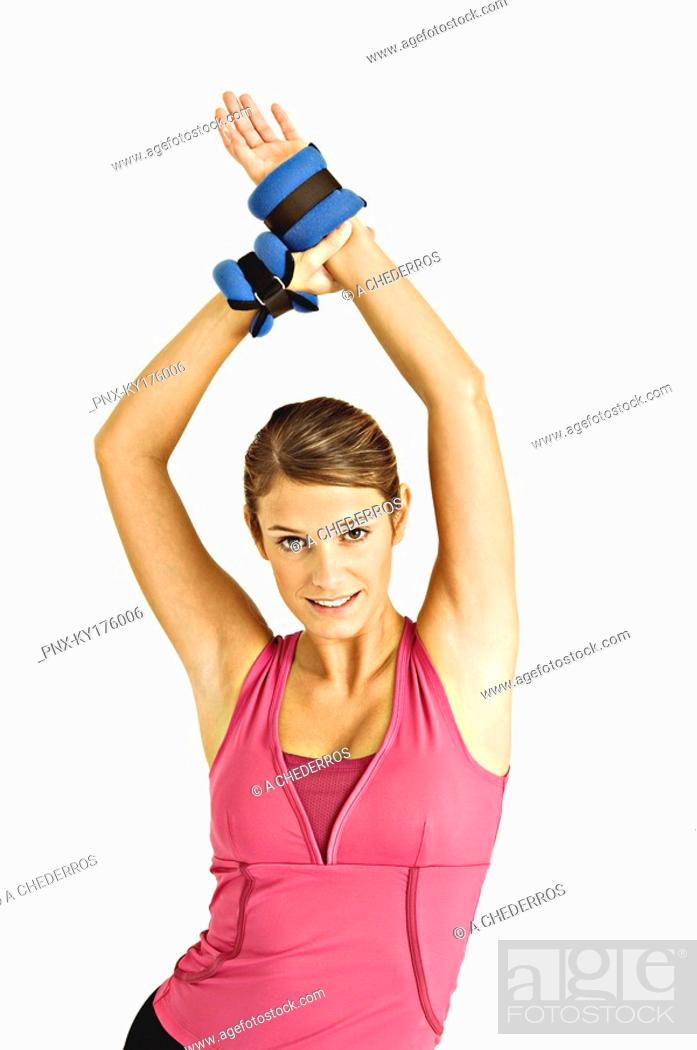 Stock Photo: Portrait of a young woman stretching with her arms raised.