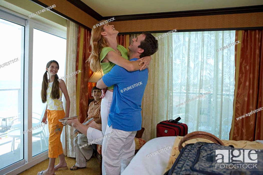 Stock Photo: Side profile of a young couple with their son and daughter in a hotel room.