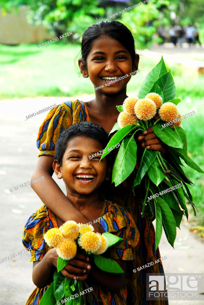 Stock Photo: Two little girls posed for photograph They sell 'Kadam flowers' at the street Dhaka, Bangladesh 2007.