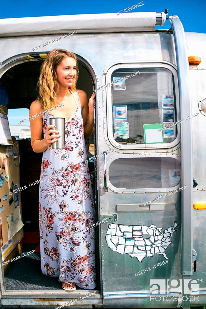 Stock Photo: Young woman wearing maxi dress looking out from airstream doorway.
