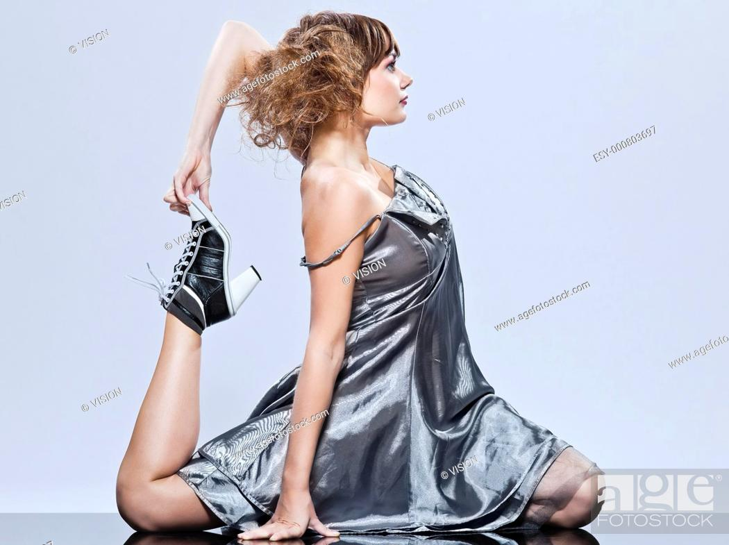 Stock Photo: beautiful young caucasian woman girl evening dress supple stretching on studio isolated plain background.
