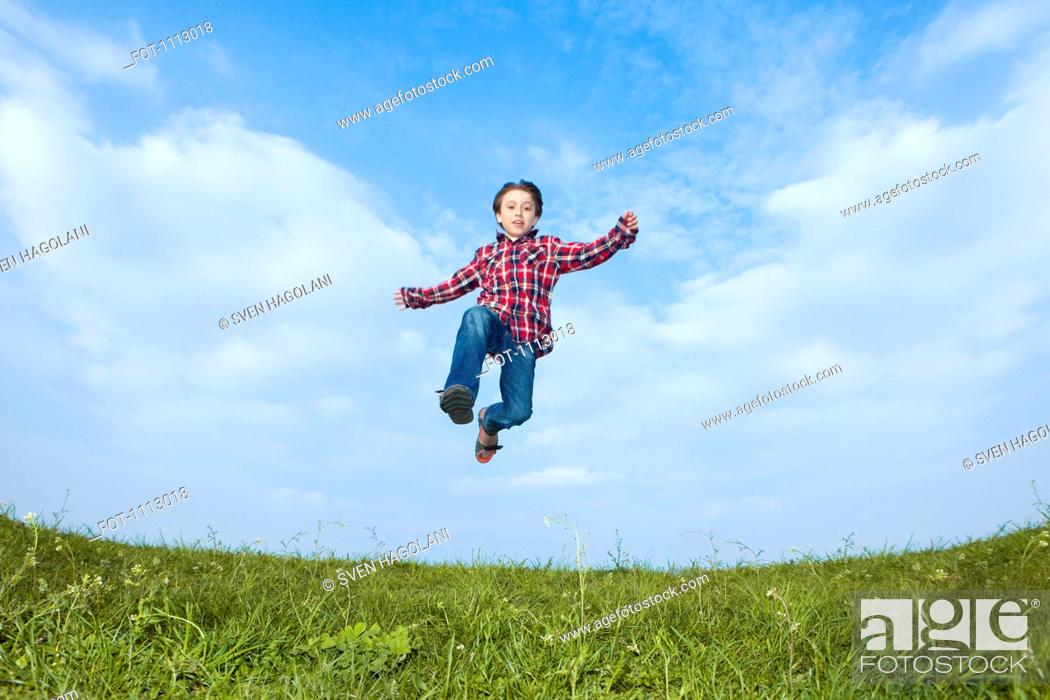 Stock Photo: A boy jumping in the air.