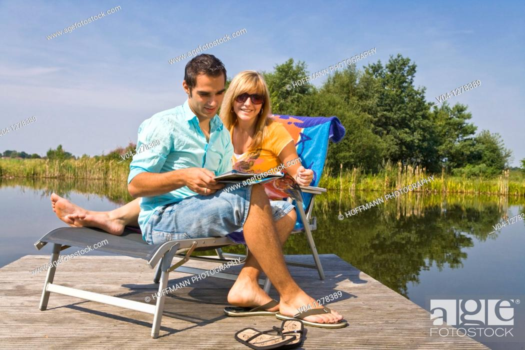 Stock Photo: A young couple studying a magazine at a lake, Germany, Europe.