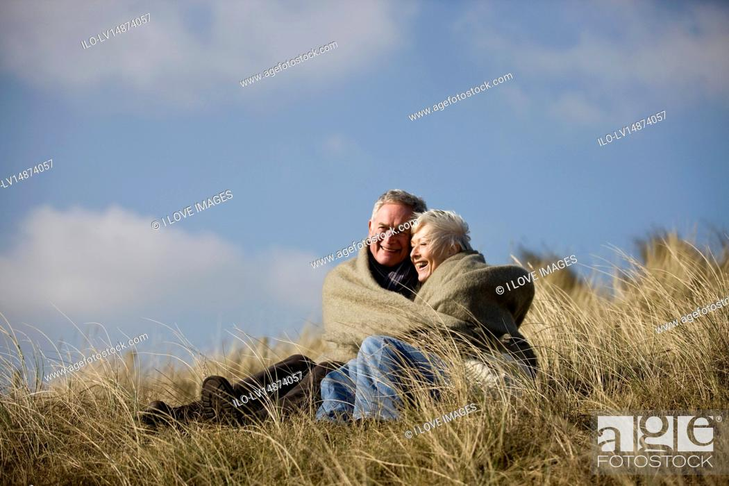 Stock Photo: A senior couple sitting amongst the sand dunes, wrapped in a blanket.