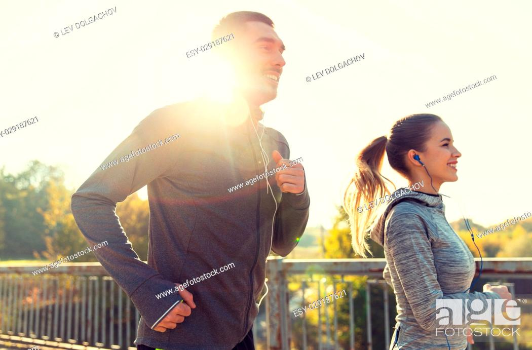 Stock Photo: fitness, sport, people and lifestyle concept - happy couple with earphones running outdoors.