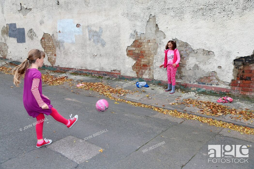 Imagen: Girls playing football in street.