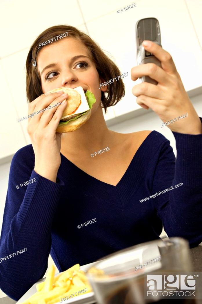 Stock Photo: Close-up of a young woman eating a burger and looking at a mobile phone.