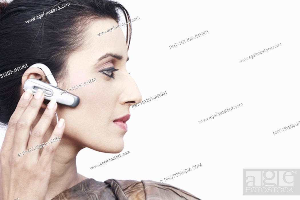 Stock Photo: Close-up of a young woman wearing a hands free device.