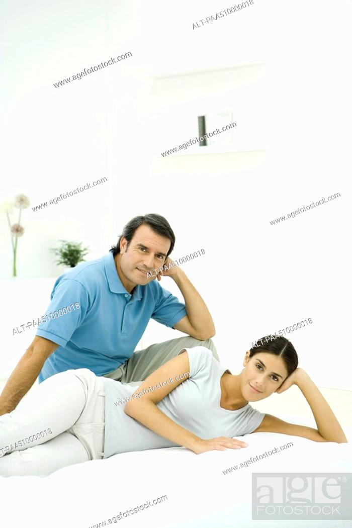 Stock Photo: Couple relaxing together on bed, both smiling at camera.