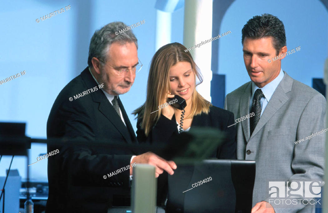 Stock Photo: Three businesspeople, businesswoman talking on phone.