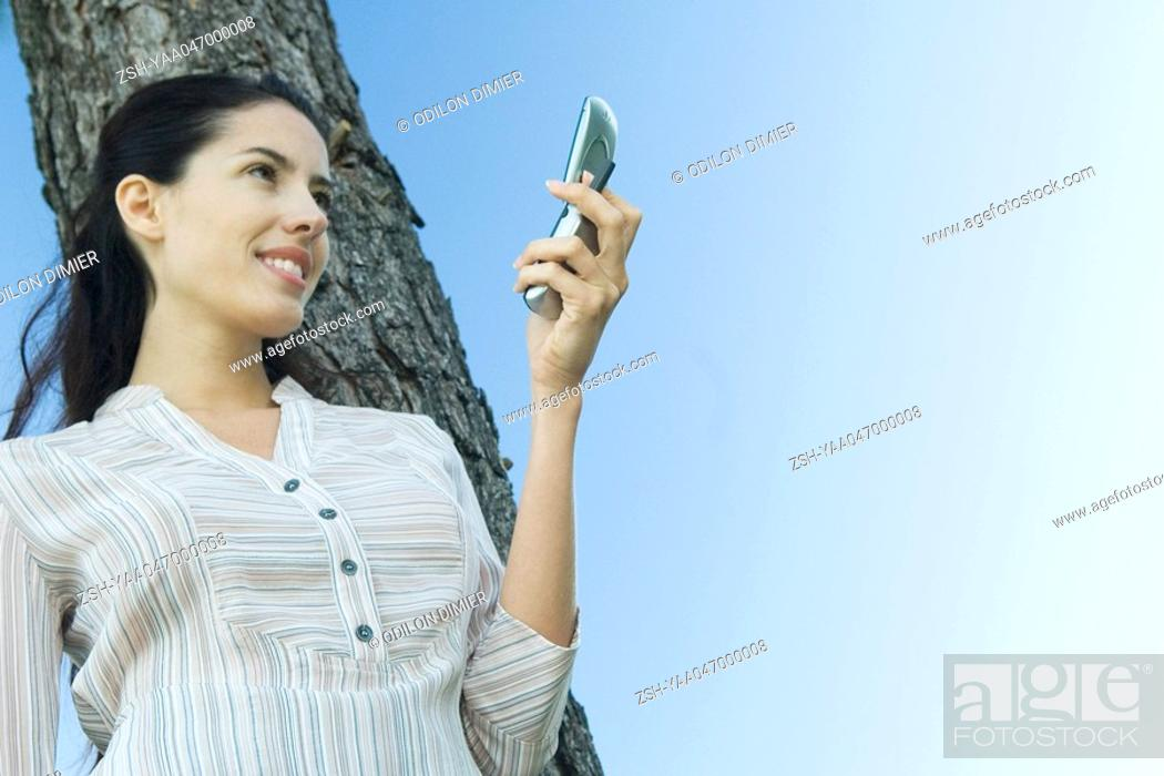 Stock Photo: Woman holding cell phone, leaning against tree, low angle view.