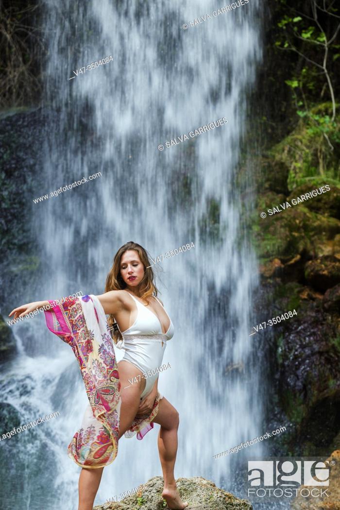 Imagen: Woman posing in a white bodysuit in front of a waterfall.