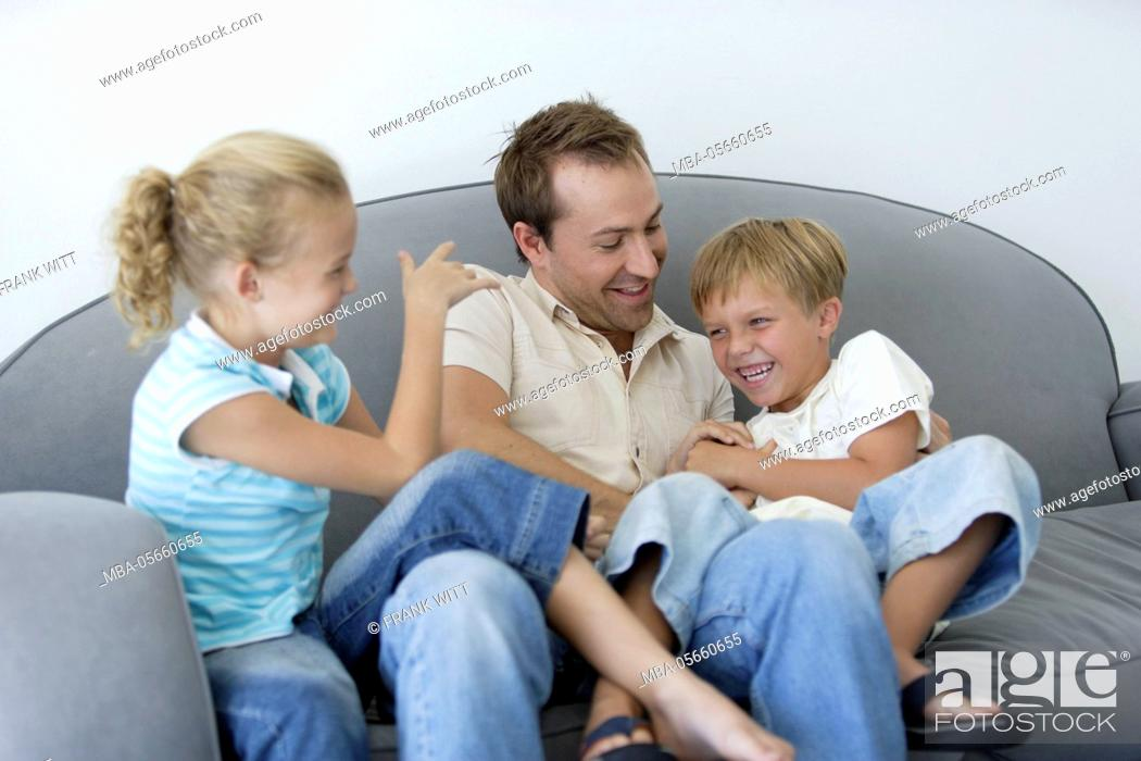 Stock Photo: Father and 2 children are romping around on sofa.