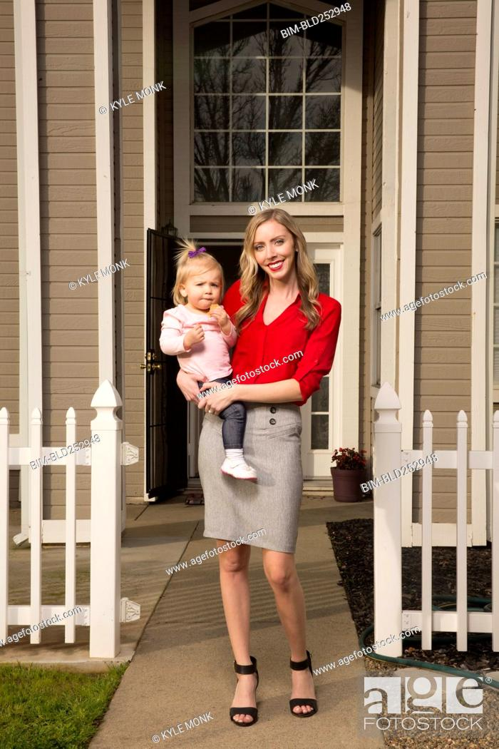 Photo de stock: Caucasian mother posing near house with baby daughter.