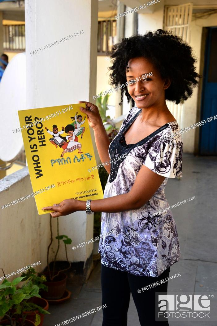 Stock Photo: Bruktawit Tigabu, founder of the Whiz Kids Workshop media company, showing a small advertisement with her cartoon heroines in front of the offices of her.
