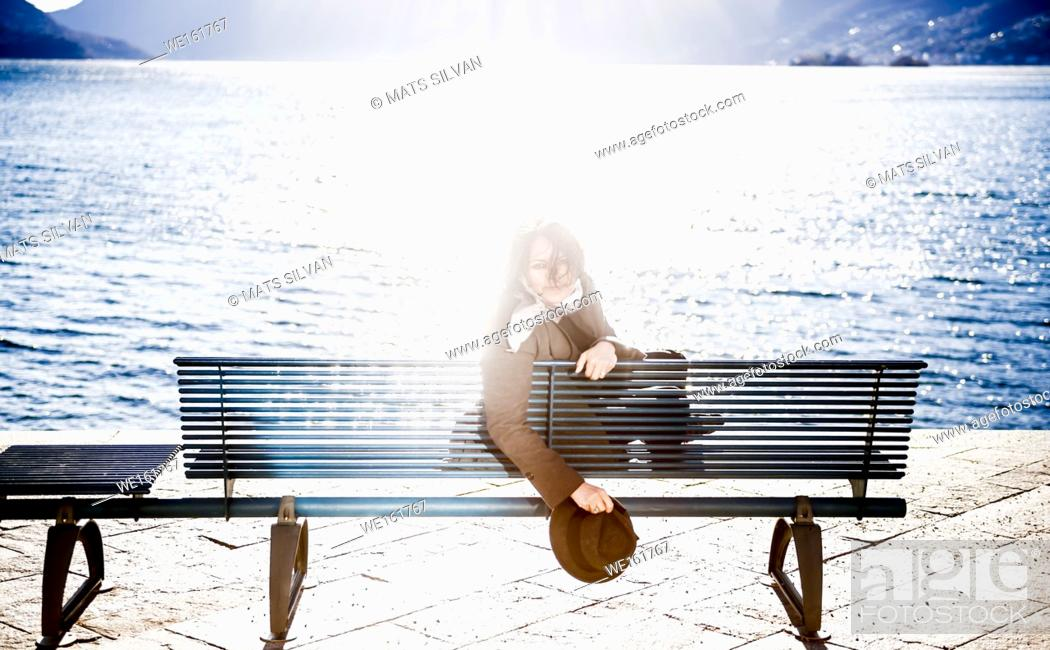 Stock Photo: Woman Sitting on a Bench on the Waterfront and Looking Back with Sun Reflection in Ascona, Switzerland.