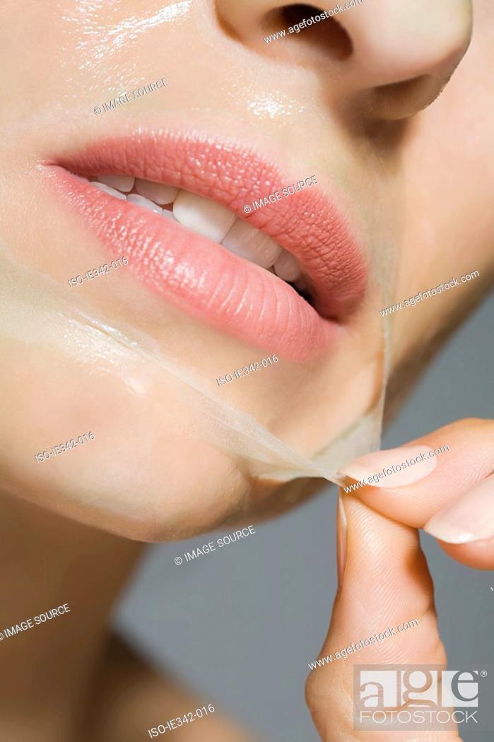 Stock Photo: Woman peeling face mask.