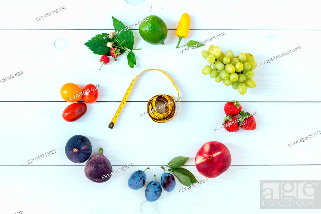 Imagen: Fitness healthy food on white wooden background (lime, strawberry, plum, figs, raspberries, grapes, peppers, peaches, tomatoes nectarines and measuring tape).