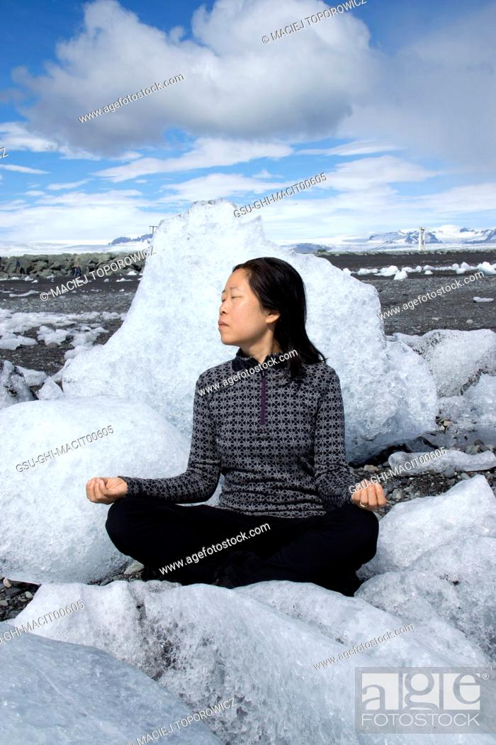 Stock Photo: Mid-Adult Woman Meditating on Beach with Large Ice Formations, Reynisfjara Beach, Iceland.