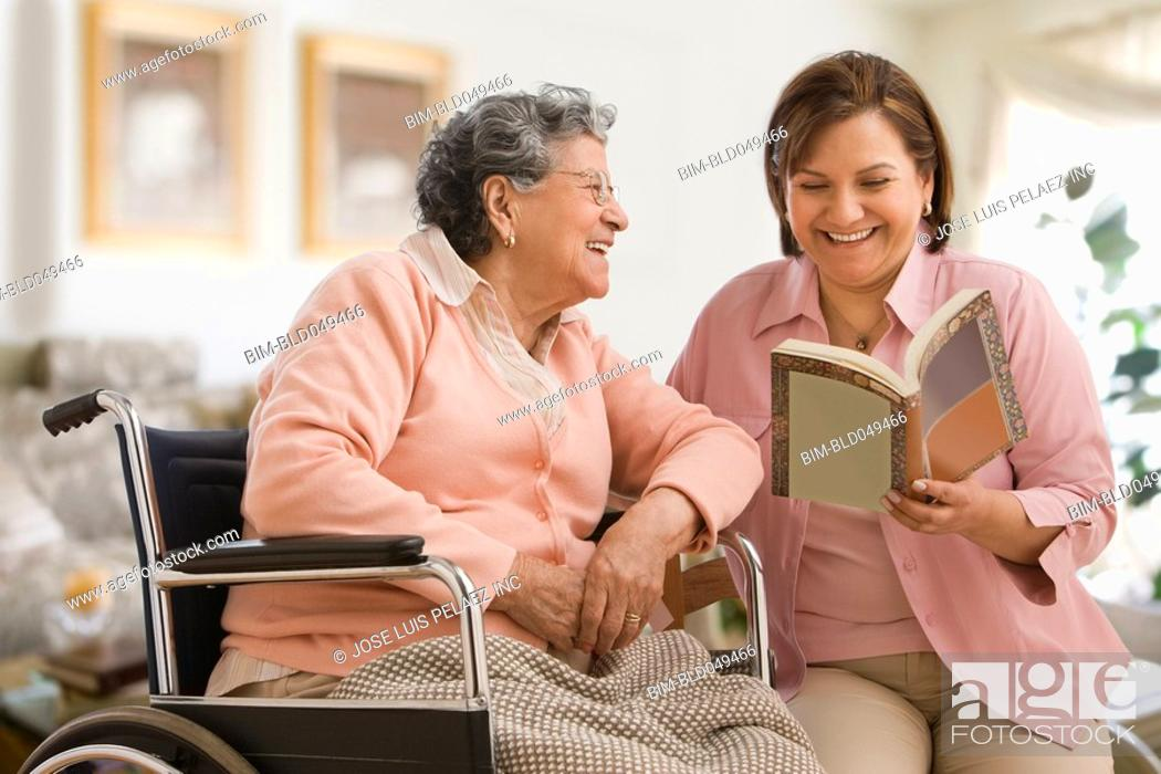 Stock Photo: Hispanic woman reading to mother.
