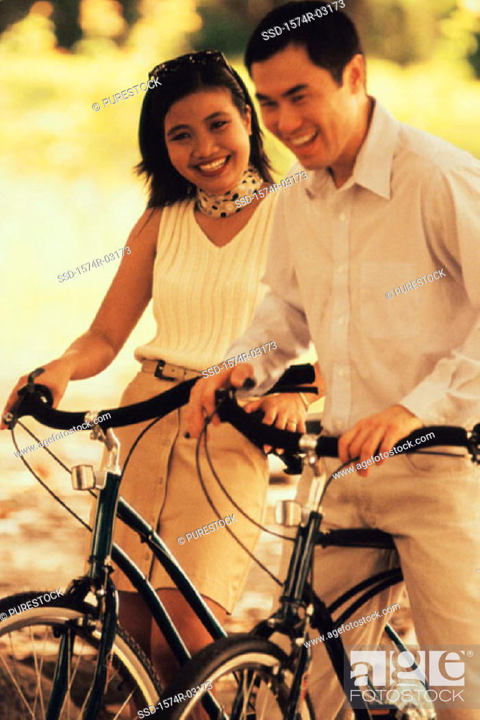 Stock Photo: Young couple standing with bicycles.