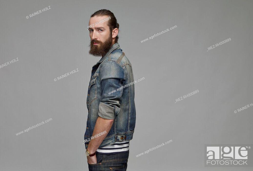 Stock Photo: Portrait of man with full beard wearing jeans jacket.