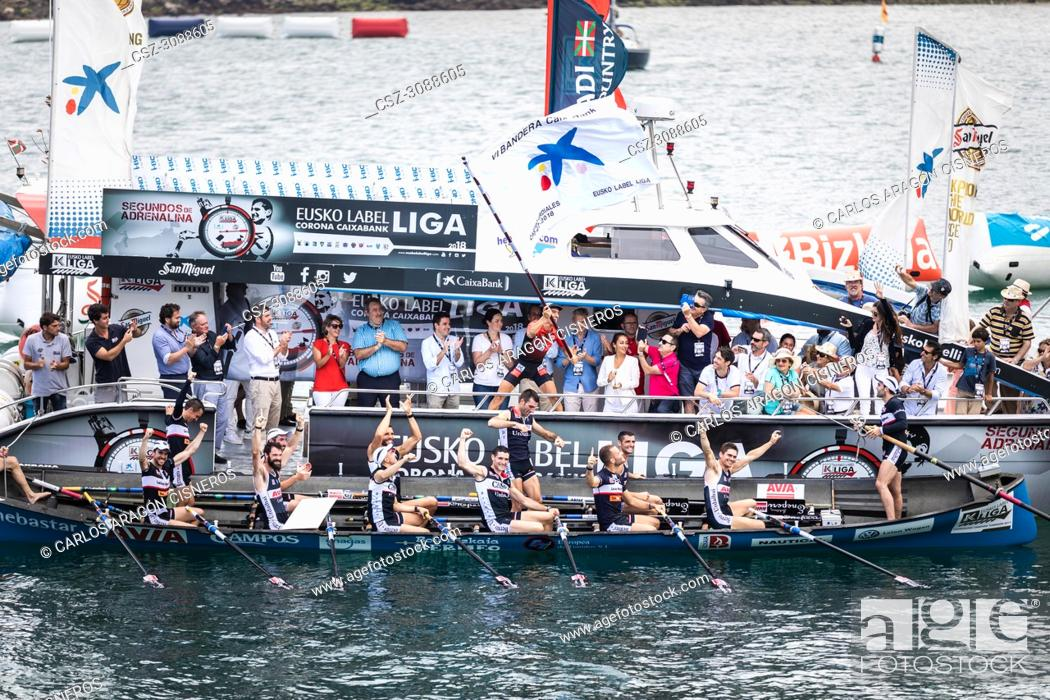 Stock Photo: CASTRO URDIALES, SPAIN - JULY 15, 2018: Competition of boats, regata of trainera, Urdaibai Avia boat with the prize after winning the competition VI Bandera.