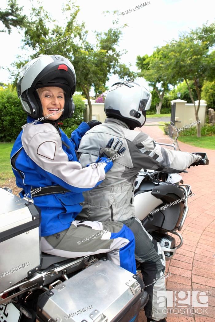 Stock Photo: Portrait of happy senior woman wearing helmet on back of motorcycle in driveway.
