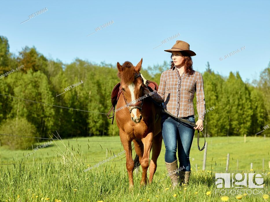 Stock Photo: Cowgirl and pony together, sunny beautiful summer day. South Finland in May.