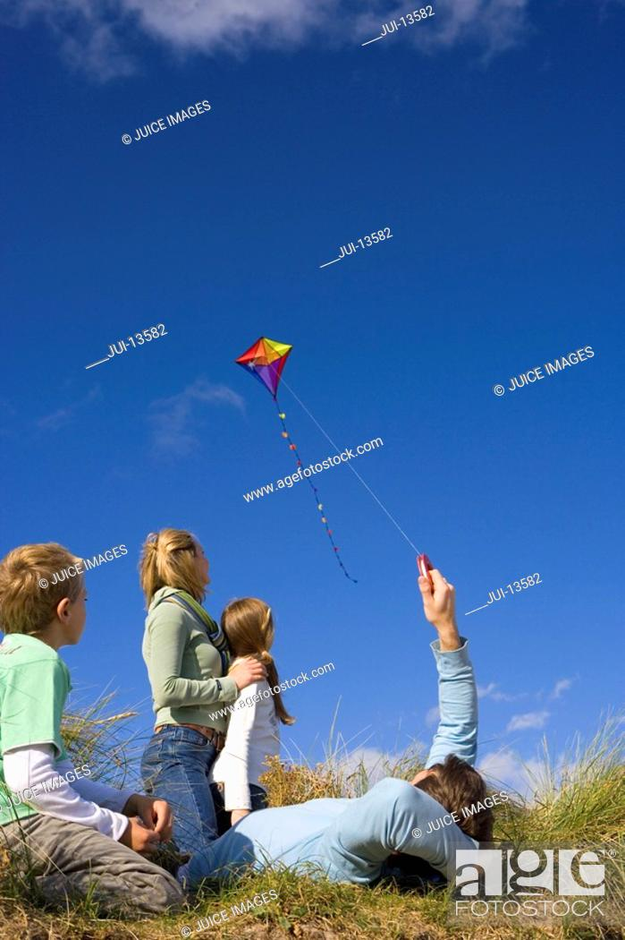 Stock Photo: Family of four flying kite whilst sitting on grass, rear view.