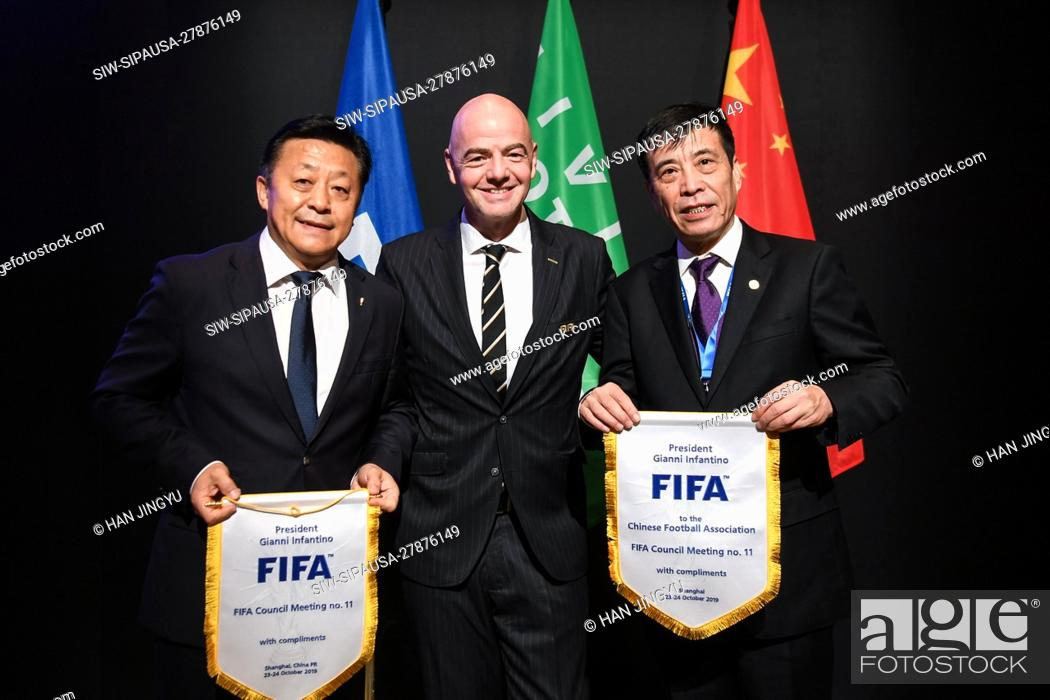 Stock Photo: FIFA president Gianni Infantino, middle, confers FIFA flag to the president of Chinese Football Association Chen Xuyuan, right.