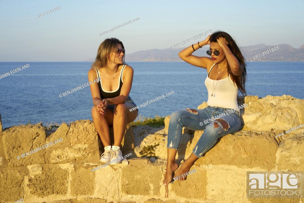Stock Photo: two friends sitting on ancient ruins at seaside, chilling, hanging out, in Chersonissos, Crete, Greece.