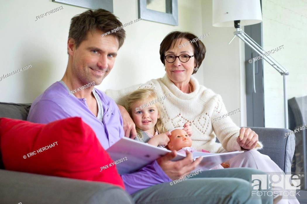 Stock Photo: Girl studying with her father and grandmother at home.