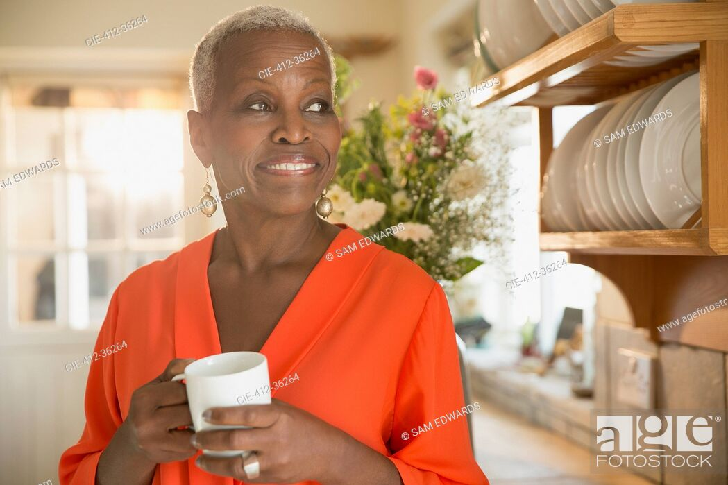 Stock Photo: Smiling senior woman drinking coffee in kitchen.