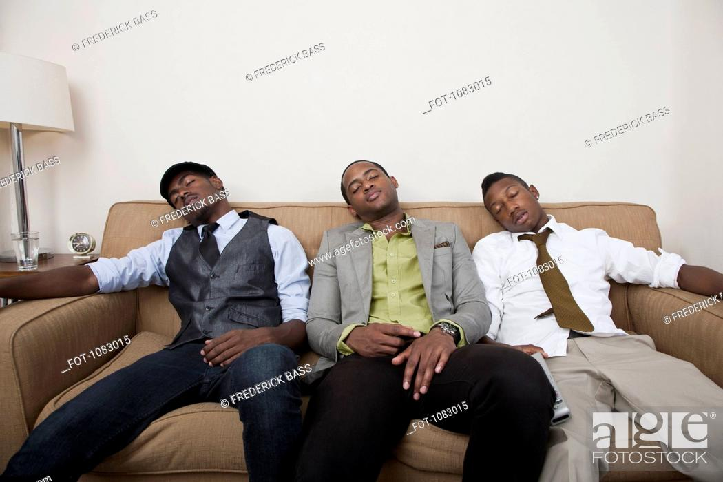 Stock Photo: Three exhausted friends asleep on a sofa.