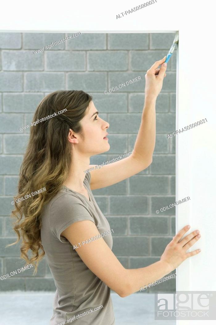 Stock Photo: Woman painting doorframe, side view.