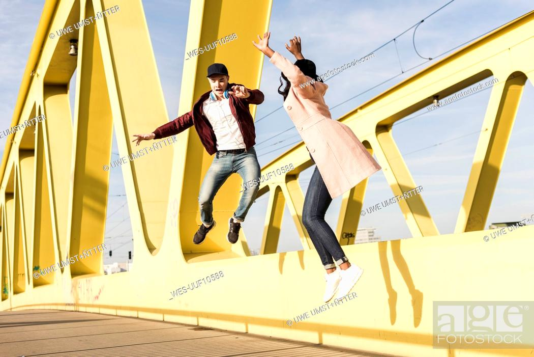 Stock Photo: Happy couple jumping on bridge.